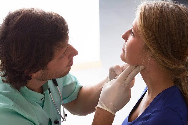 un medico examinando la garganta de una mujer