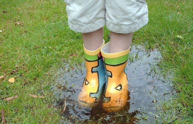 chico con botas de agua en un charco