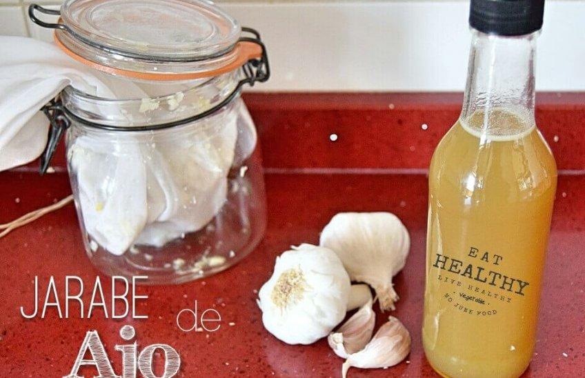botella con jarabe de ajo junto a unos ajos