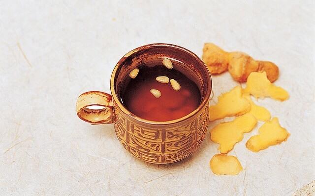 taza con te de jengibre junto a unos cachos de la raiz