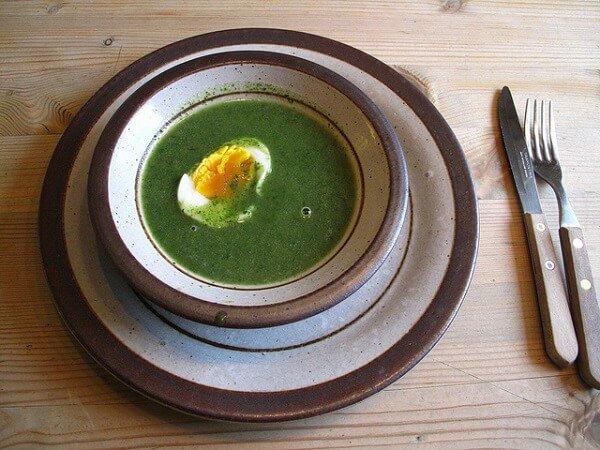 plato de sopa de ortiga y cubiertos