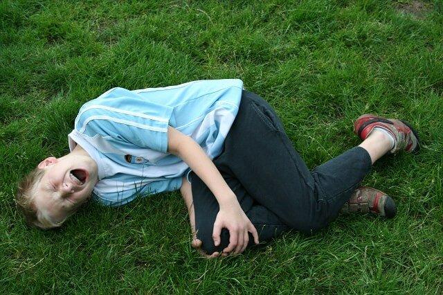 nino con golpe en la rodilla tumbado en el cesped
