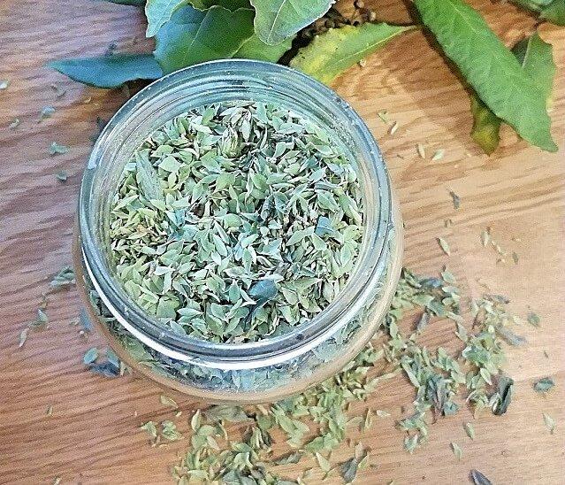 oregano seco en bote de cristal junto a unas hojas de laurel