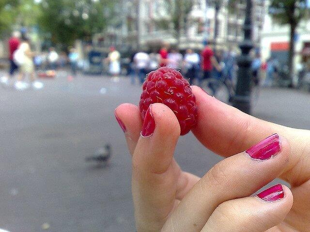 mano de chica que sostiene una frambuesa
