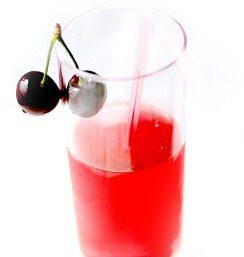 Vaso con zumo de cerezas decorado con unas cerezas