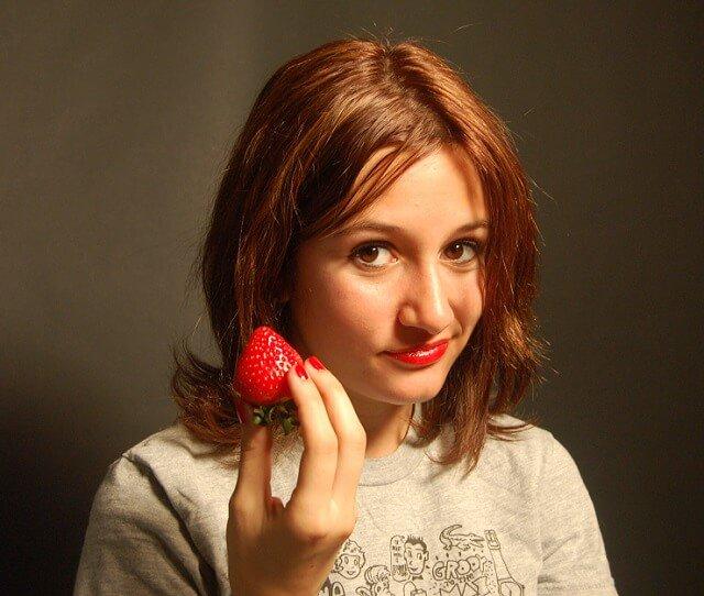 Chica joven con una fresa en la mano