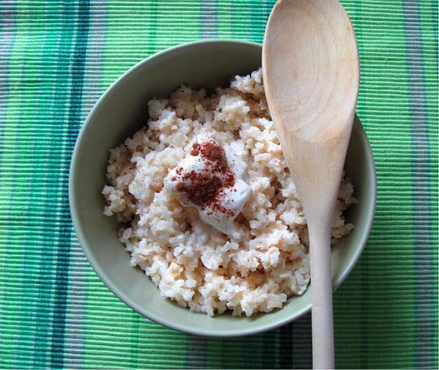 Cuenco con arroz con leche y una cuchara de madera