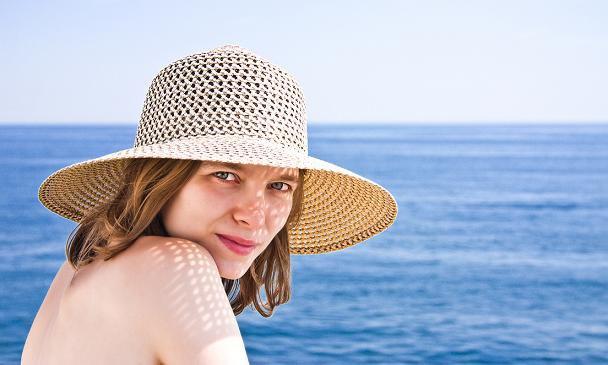 mujer bella con sombrero al lado del mar