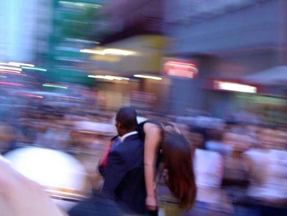 hombre de traje que lleva al hombro a una chica desmayada