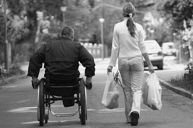 hombre en silla de ruedas junto a mujer que lleva unas bolsas