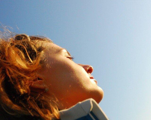 chica con los ojos cerrados mirando al sol