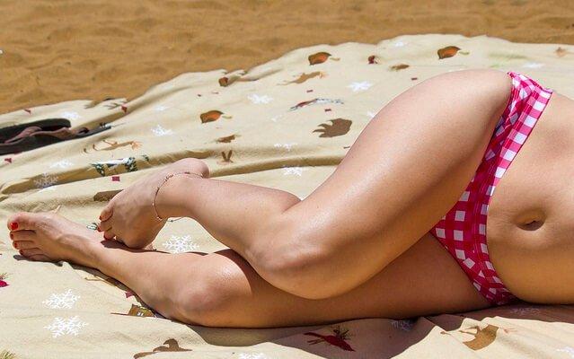 chica tumbada en la playa solo se ven las piernas