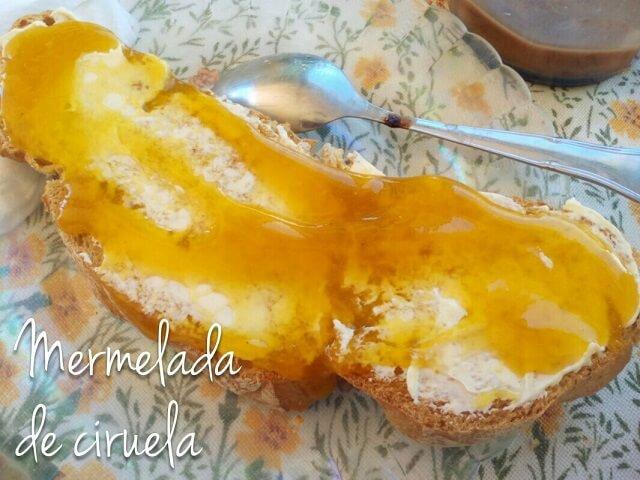 tostada conmermelada de ciruela en un plato junto a una cuchara y una taza
