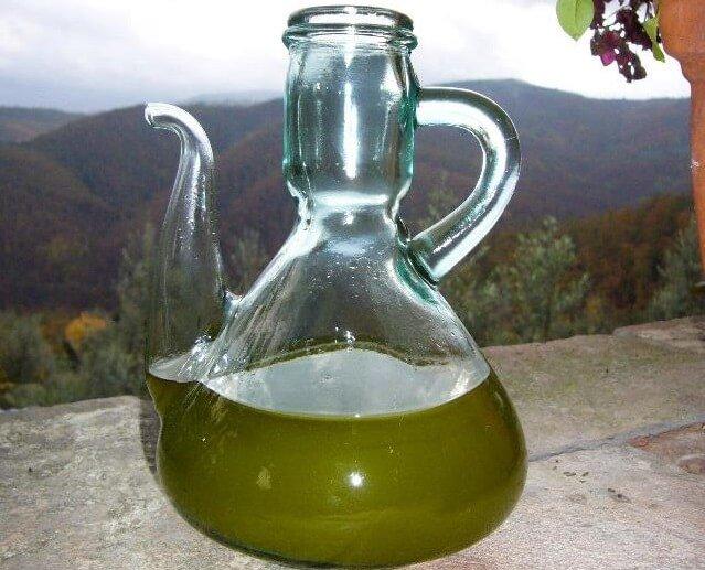aceite de oliva recien extraido en envase de cristal junto a una bonita vista