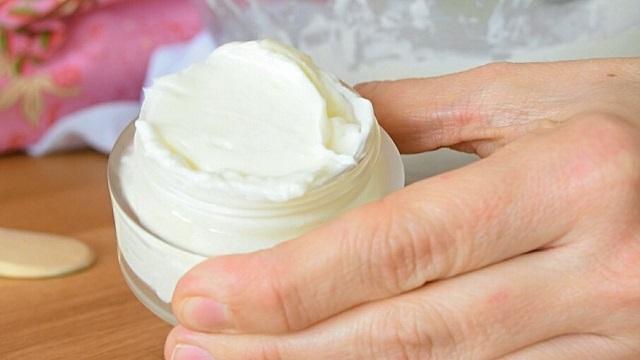 bote de cristal con crema antiarrugas sujeta por una mano