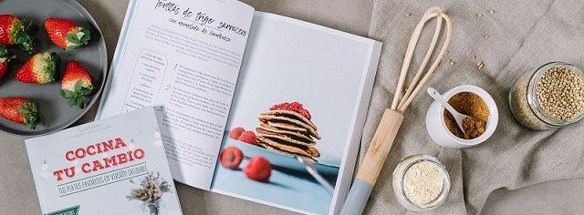 libro cocina tu cambio junto a unas fresas y utensilios de cocina