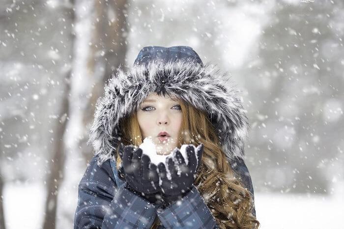 una chica con capucha bajo la nieve