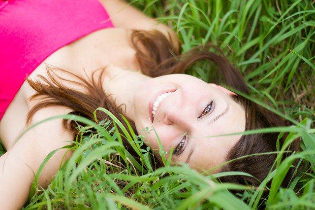 chica tumbada en el cesped con cara sonriente