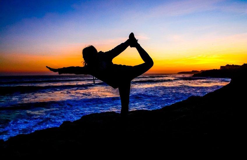 chica haciendo yoga en la playa